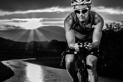 Triathlet faisant un cycle dans le lever de soleil Photo stock