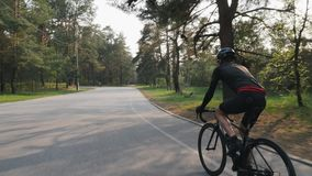 Triathlete που φορά το μαύρο οδηγώντας ποδήλατο εξαρτήσεων στην κατάρτιση πάρκων για μια φυλή Η πίσω πλευρά ακολουθεί τον πυροβολ απόθεμα βίντεο
