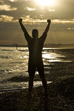 Triathlete celebrating on beach. Stock Images