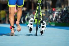 Triathlete courant avec votre vélo la zone de transition Image libre de droits