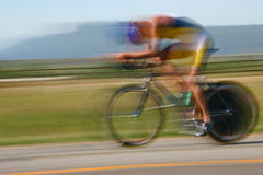 Triathlete Cyclist Blur. A triathlete pedals past in a blur Stock Photo