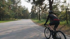 Triathlete, das schwarzes Ausstattungsreitfahrrad im Parktraining f?r ein Rennen tr?gt R?ckseite folgen Schuss Triathlonkonzept stock video