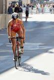 Triathlete Elena Danilova stående övre cykla Arkivbild
