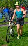 Triathlete femminile all'estremità della fase di riciclaggio con la bicicletta Immagini Stock