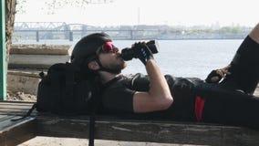 Triathlete im schwarzen Trikot und in Trinkwasser der kurzen Hosen von der Flasche auf der Bank, die Sonne genießt Tragende Sonne stock footage