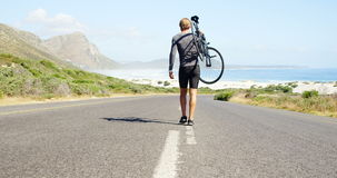 Triathlete man carrying cycle in the countryside road