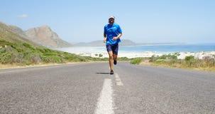 Triathlete man som joggar i bygdvägen lager videofilmer