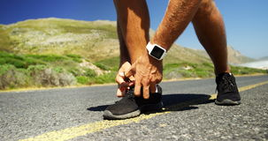 Triathlete man tying his shoe lace in the countryside road stock video footage