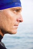 Triathlete in profile. A color portrait photo of a handsome mature male triathlete or swimmer standing in profile and wearing a blue swimming cap Royalty Free Stock Images