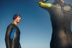 Triathlete que se coloca con su engranaje de la natación encendido Imagenes de archivo