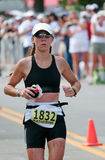 Triathlete Runner. Triathlete female runner is on the last leg of an ironman running a marathon Royalty Free Stock Photo