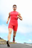 Triathlete running man. Triathlon running man. Triathlete runner training on Hawaii for ironman. Male athlete running in red compression clothing, shorts and top Royalty Free Stock Photos