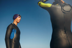 Triathlete standing with his swimming gear on Stock Images