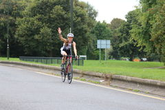 Triathlete triathlon healthy exercise sport cycling. A female triathlete waves happily during the open road cycling section of a triathlon in Crawley, Sussex, UK Royalty Free Stock Photo