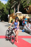 Triathlete triathlon healthy exercise sport cycling. Triathlete Katie Synge, GB, dismounts her bike ready to enter transition after the cyling stage of the half Royalty Free Stock Image