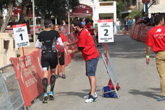 Triathlete triathlon healthy exercise sport running. A triathlete collects a lap band to show how far he has run during at the half iron man distance triathlon Stock Photo