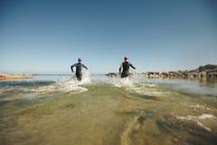 2 triathletes спеша в воду для части заплыва гонки Стоковое Фото