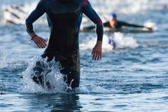 Triathletes die uit van het water op triatlon lopen stock afbeeldingen