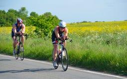 Triathletes en la etapa de ciclo del camino de los campos y de los árboles del triathlon en fondo Fotos de archivo