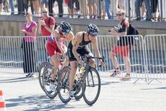 Triathletes Hanna Philippine and Mariya Shorets cycling a hill Stock Photography