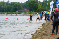 Triathletes Heading Out. Two triathletes begin the first leg of their race, wading into the water of Pewaukee Lake during the start of the 2014 Sprint Triathlon Stock Photo