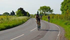 Triathletes på vägen som cyklar etappen av triathlonfält och träd i bakgrund Arkivfoto