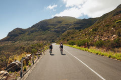 Triathletes practicing cycling on open country road Royalty Free Stock Image