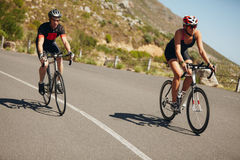 Triathletes riding bicycle on open road Stock Images