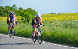 Triathletes on road cycling stage of triathlon fields and trees in background. Stock Photos