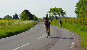 Triathletes on road cycling stage of triathlon fields and trees in background. Stock Photo