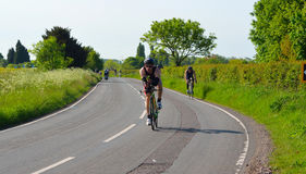 Triathletes on road cycling stage of triathlon fields and trees in background. Royalty Free Stock Photography