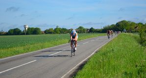 Triathletes on road cycling stage of triathlon riding in both directions. Stock Images