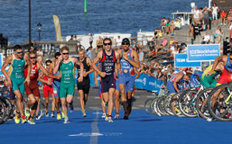 Triathletes start running after the cycle part in the transition stock photo