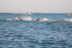 Triathletes triathlon healthy exercise sport swimming. Triathletes swimming in the sea during a triathlon in Mallorca watched by safety crews on paddle boards Royalty Free Stock Photography