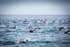 Triathletes w wodzie w Ironman triathlon rywalizaci przy Calella plażą Obrazy Stock