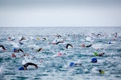 Triathletes w wodzie w Ironman triathlon rywalizaci przy Calella plażą Zdjęcia Stock