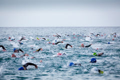 Triathletes in water in the Ironman triathlon competition at Calella beach Stock Photos