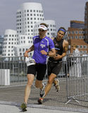 Triathlon. In this photo two participants of the Düsseldorf T³ Triathlon, can be seen running through the Medienhafen. In the background are the famous Gehry Stock Photo