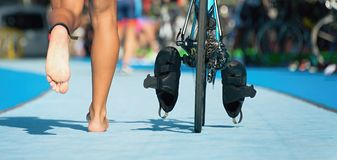 Triathlon bike the transition zone. The triathlonist runs on a bicycle Stock Photo