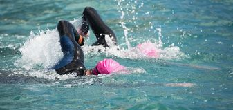 Triathlon long distance swimming. People in wetsuit swimming at triathlon royalty free stock photography
