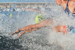 Triathlon participants running into the water for swim portion of race Stock Photo