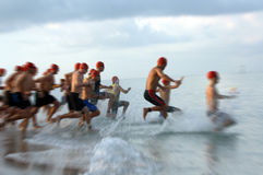 Triathlon swim race blur. A motion blur of the start of a swim race into the ocean stock images