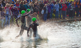 Triathlon swimmers entering open water swim stage. Stock Photo