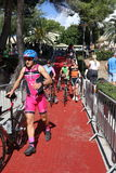 Triathlon triathlete sport healthy exercise cycling. Triathletes push their bikes as they enter transition at Challenge Peguera, a half distance ironman race, in Stock Photo