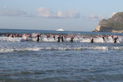 Triathlon triathlete sport healthy exercise swim. Triathletes battle against waves as they enter the sea for the swimming leg of Challenge Peguera, a half Royalty Free Stock Images