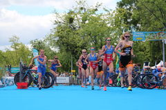Triathlon triathletes sport healthy exercise cycling running. Female triathletes leave transition for the run after the cycling leg at the European Triathlon Royalty Free Stock Photo