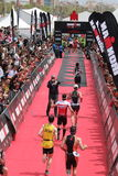 Triathlon triathletes sport healthy exercise running finish line. Triathletes running down the red carpet to the finish line at Ironman 70.3 Barcelona Stock Photo