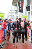 Triathlon triathletes sport healthy exercise swimming. Triathletes leave the water to remove their wetsuits and head for transition after a swimming leg at the Stock Image