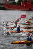 Triathlon triathletes sport healthy exercise swimming. Safety crews lift the starting rope for the start of a swim leg at the 2016 London Triathlon in Docklands Royalty Free Stock Photos
