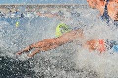 Triathlonteilnehmer, die in das Wasser für Schwimmenteil des Rennens laufen stockfoto
